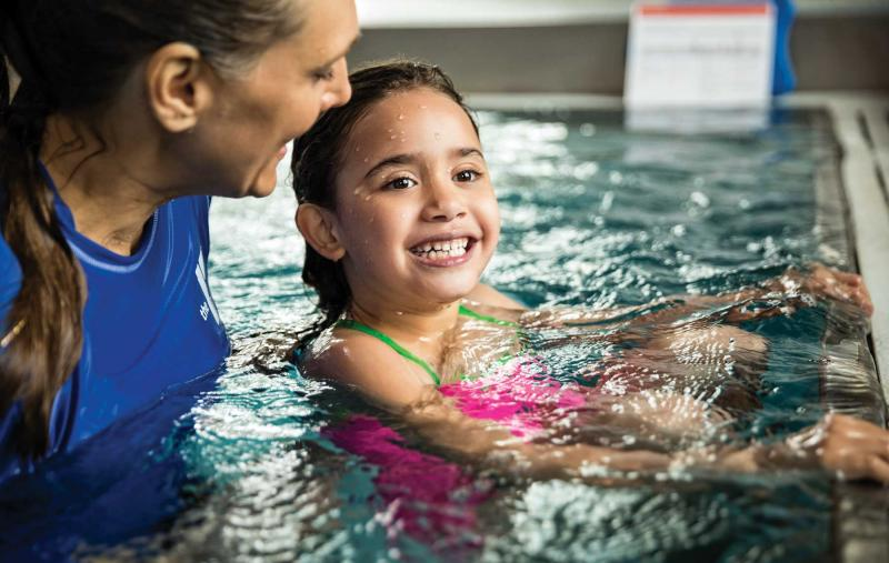 A girl smiles in the pool while learning to swim during a YMCA swimming lesson.