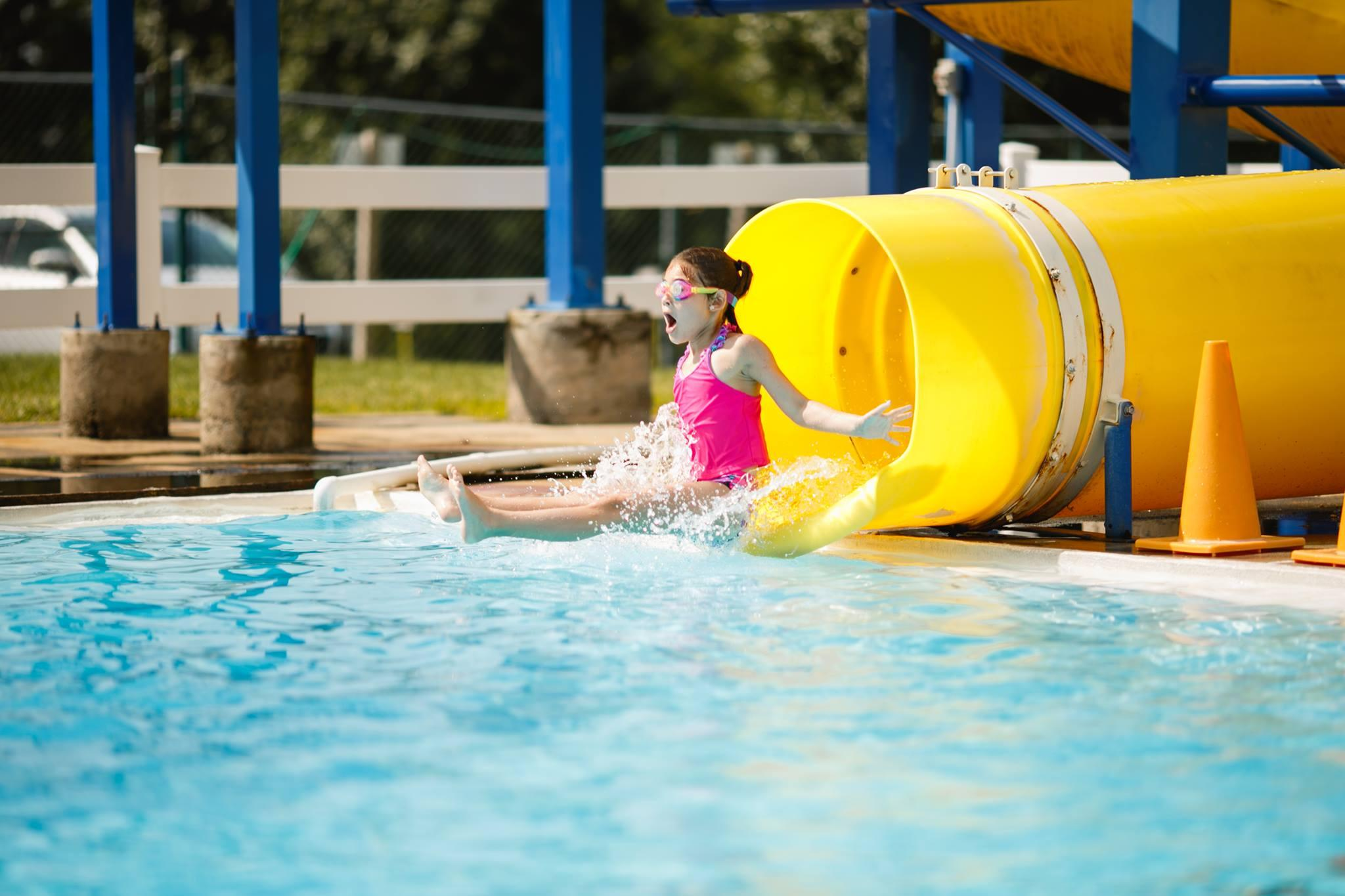 A camper at Brandywine YMCA summer camp goes down the outdoor swimming pool water slide during camp swim time.