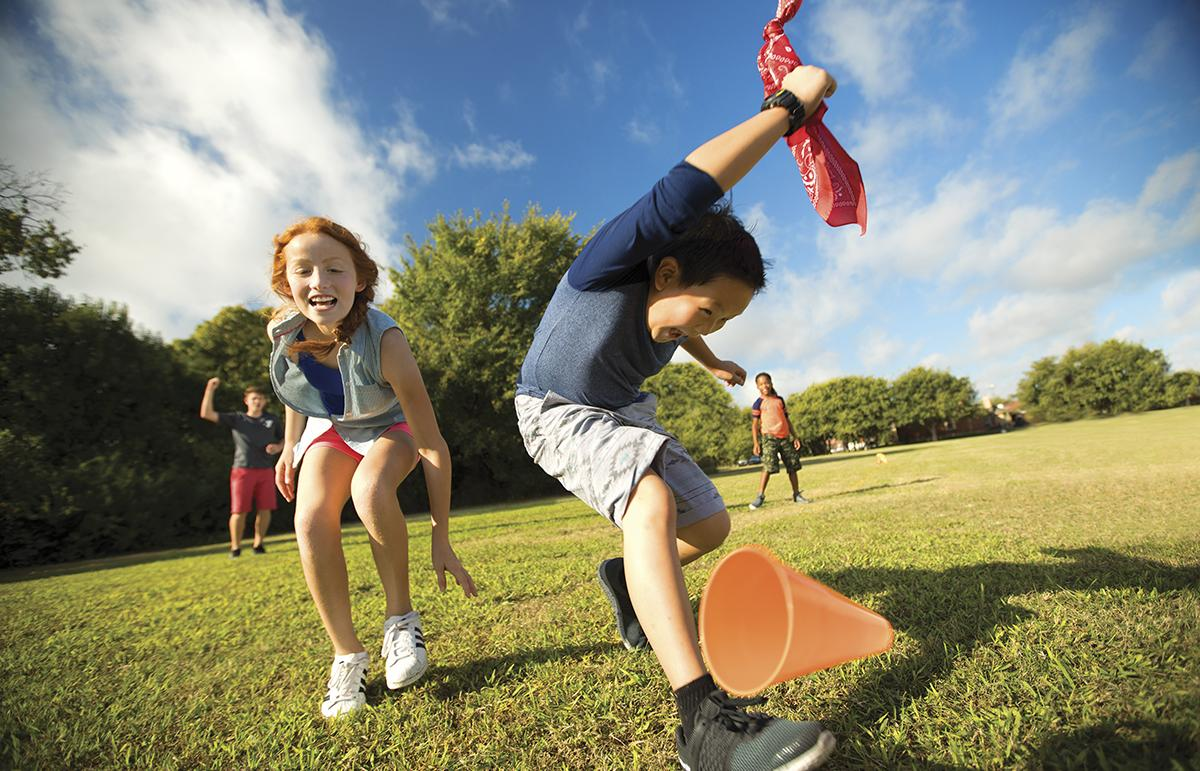 A boy and girl play outside during camp at the YMCA.