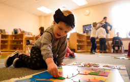A child plays with a puzzle in the Montessori classroom at West Chester Area YMCA in West Chester, PA.