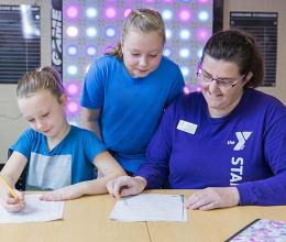 Kids do their homework with a YMCA staff person during their after school program at the YMCA