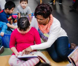 A volunteer and student read stories together during a program to honor Martin Luther King, Jr Day at the YMCA in Chester County.