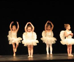 Three young girls in ballet costumes participate in a dance recital at the YMCA