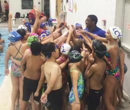 Children and teens on the Lionville Community YMCA swim team huddle up before a swimming meet.