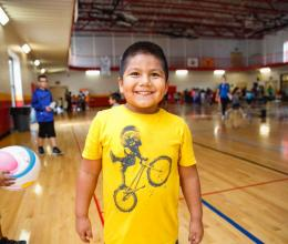 Boy smiling in the gym during the after school care program at  Oscar Lasko YMCA & Childcare Center
