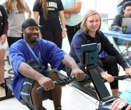 Young man and women test rowing exercise equipment at the YMCA.